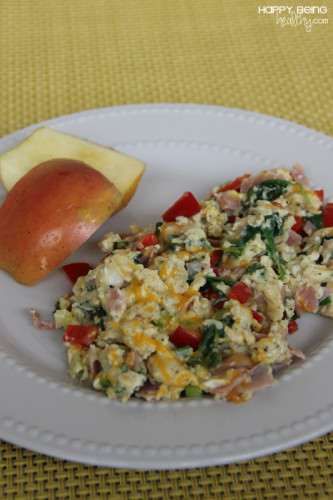 Eggs scrabled with veggies and an apple on the side
